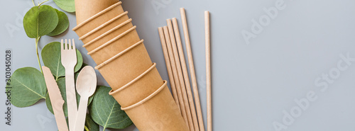 Foto eco natural paper cups, straws, wooden cutlery flat lay on gray background