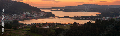 Serene dusk panorama of the medieval fishing town of Pontedeume with its iron and stone bridge orange sky La Coruña Galicia