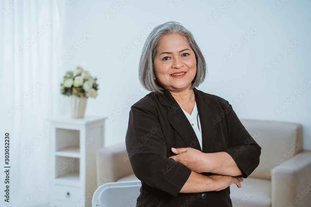 Fototapeta Confident senior business woman standing with crossed hands