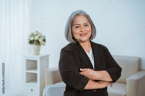 Fotografia, Obraz  Confident senior business woman standing with crossed hands