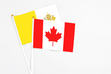 Canada And Vatican City Stick Flags On White Background. High Quality Fabric, Miniature National Flag. Peaceful Global Concept.White Floor For Copy Space.