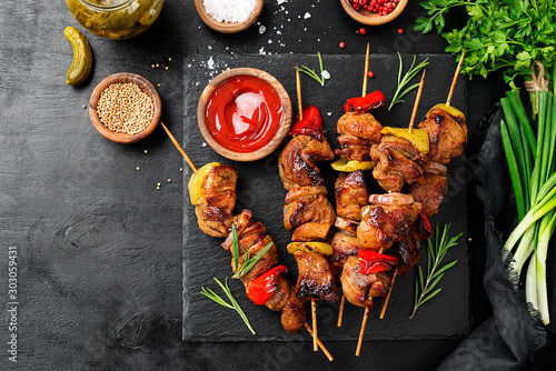 Pinturas sobre lienzo  Kebabs - grilled meat skewers, shish kebab with vegetables on black wooden background