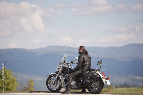 Handsome bearded biker with long hair in black leather jacket and sunglasses sit Wallpaper Mural