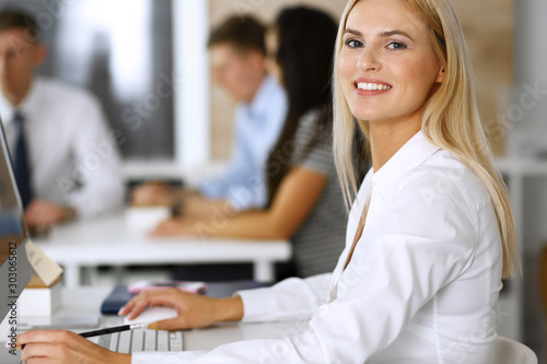 Canvas Prints Textures Business woman using computer at workplace in modern office. Secretary or female lawyer smiling and looks happy. Working for pleasure and success