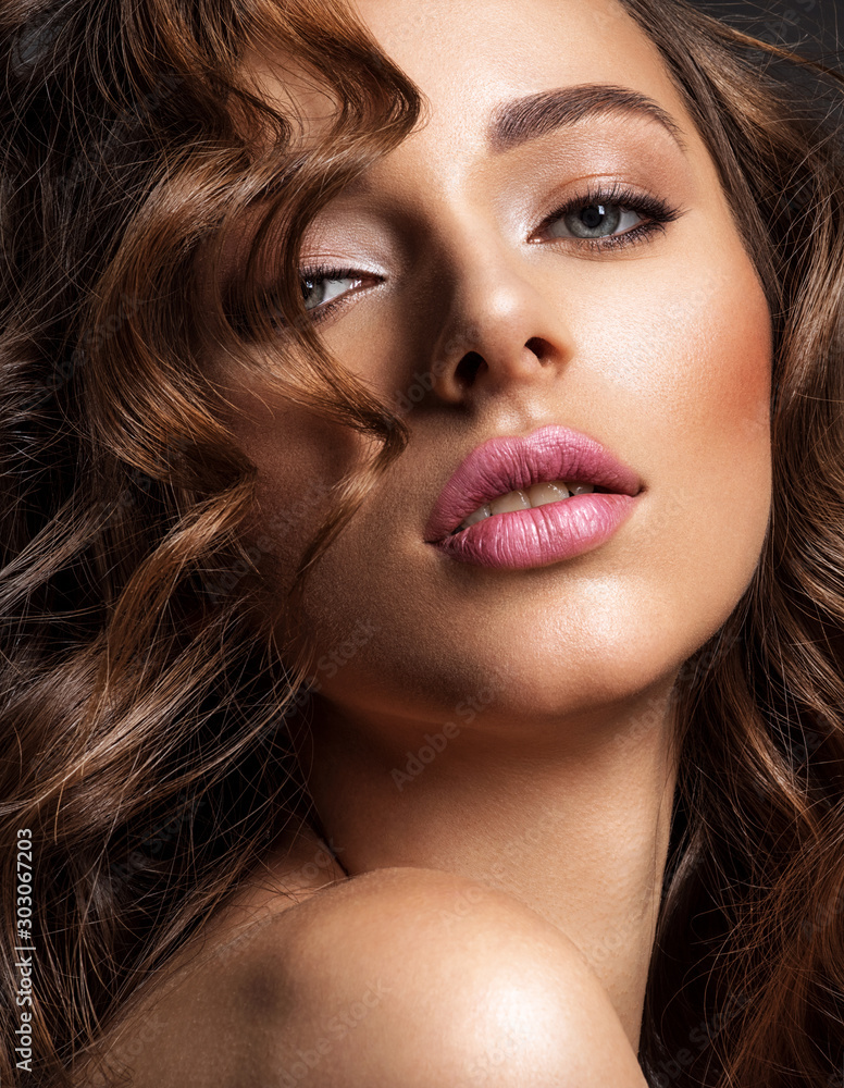 Fototapeta Beautiful woman with brown hair. Beautiful face of an attractive model with fashion makeup. Woman with beauty long curly  hair. Closeup portrait of a caucasian female. Stunning girl.