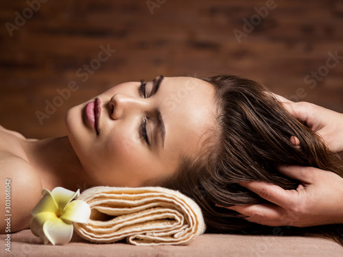 Masseur doing massage the head and hair for an woman in spa salon Poster Mural XXL