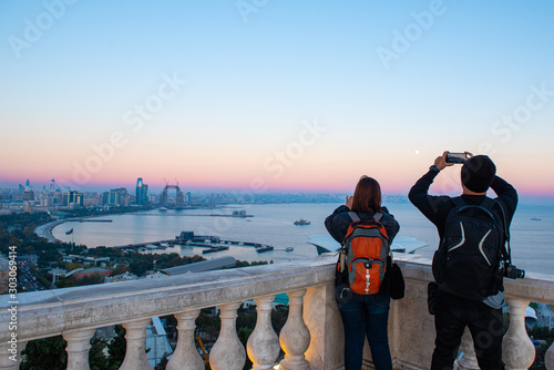 Leinwand Poster  Couple traveler use smart mobile phone and camera take photo of view of Baku caspian sea and Baku sky scape view in sunset at Buku view point with copy space