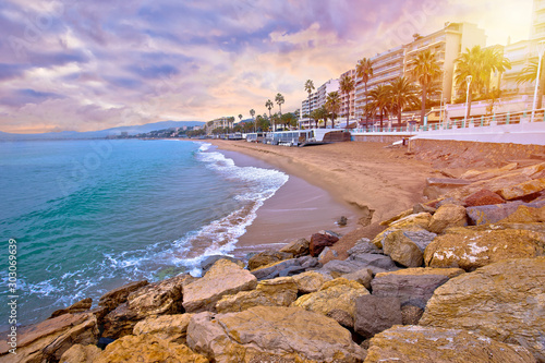 Cannes. Idyllic palm waterfront and sand beach in Cannes sun haze view