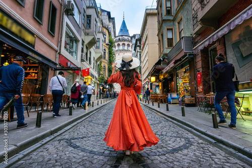 Woman standing at Galata tower in Istanbul, Turkey. Wallpaper Mural