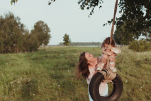 Happy Mom And Daughter Swing On A Wheel Against The Background Of Summer Nature.