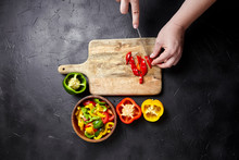 Pepper Cutting. Hands, Knife And Red, Green, Yellow Bell Peppers, Wooden Chopping Board And Bowl On Black Background. Pieces Of Sweet Peppers.  Cooking Diet Vegetable Salad, Healthy Food, Top View