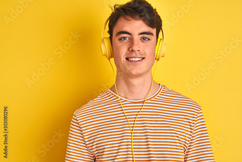 Fototapeta Teenager boy wearing headphones over isolated yellow background with a happy and cool smile on face. Lucky person. obraz