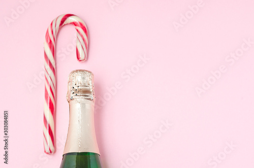 Holiday Bottle of champagne and candy canes over pink background. Christmas and New Year celebration. Copy space. Bottle with Sparkling Wine and candy canes