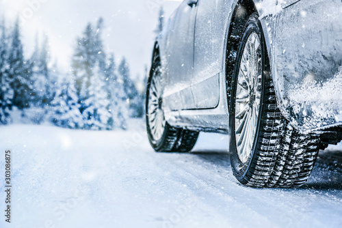 Fotografiet  Winter tire. Car tire on snow road. Tires on snowy road detail.