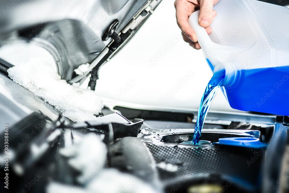 Fototapety, obrazy: Pouring antifreeze.  Antifreeze liquid for washing car screen.