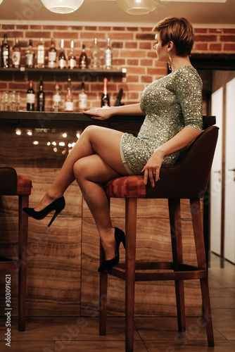 Beauty young woman portrait waiting someone at a bar. Plus size girl in a glitter party dress alone in the cafe. - 303091621
