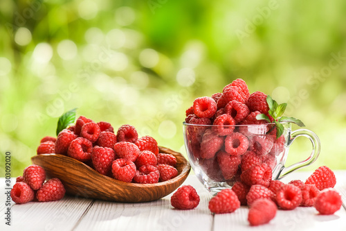 Fototapeta Raspberry in wooden bowl and glass cup full of fresh strawberries with mint leaf. obraz na płótnie