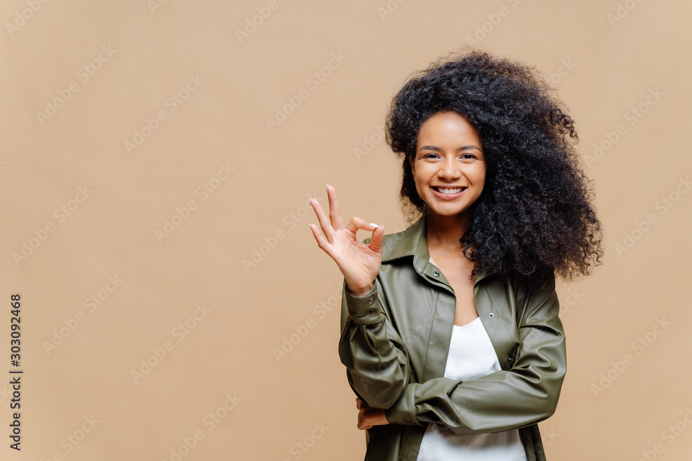 Fototapeta Indoor shot of pleasant looking curly woman has pleasant smile, makes okay gesture, excellent sign, gives approval, dressed in fashionable leather shirt, isolated over brown wall, blank space on left
