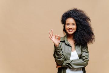 Indoor shot of pleasant looking curly woman has pleasant smile, makes okay ge...