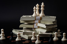 Income Inequality, Class Struggle In Capitalism And Social Issue Concept Theme With Large Group Of Chess Pawns Representing The Poor Separated From The Wealthy Who Are Sitting On A Pile Of Money