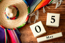 Celebrating Cinco De Mayo And Mexican Fiesta Conceptual Idea With Authentic Hat (sombrero), Traditional Colourful Rug (serape) And Block Calendar Set To May 5th On Wood Background