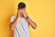 Young indian man wearing white t-shirt standing over isolated yellow background rubbing eyes for fatigue and headache, sleepy and tired expression. Vision problem