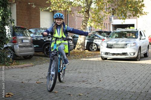 Fotografija Kind auf einem Fahrrad biegt in eine Richtung ab