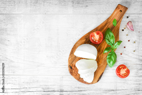 Photographie Fresh finest tomatoes on white rustic board with basil and mozzarella cheese top view