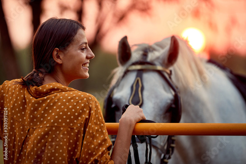 fototapeta na drzwi i meble Pretty woman smiling in front of her horse in the sunset