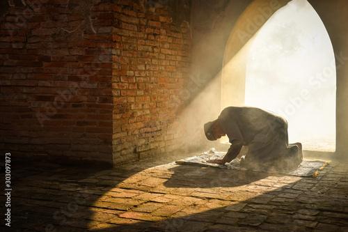 Fototapeta Muslim man praying at an old mosque in Phra Nakhon Si Ayutthaya Province, Thailand, Asian Muslims obraz na płótnie