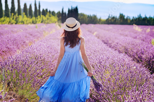 Fotografering Beautiful young woman in boho-chic style dress and hat enjoying the stroll by blooming lavender fields in Provence, France in July