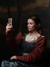 Old And New, Concept. Beautiful Young Renaissance Style Woman Taking Selfie On Phone.