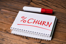 Notepad With Churn Percent Near Marker Over Desk