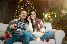 Young Couple Husband And Wife Wrapped In Plaid Watching TV Eating Popcorn On The Sofa In Room Decorated For Celebrating New Year Christmas Festive Mood