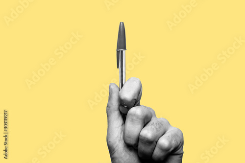 Obraz Concept of freedom of speech and information, stop censorship. Hand holding a pen in sign of protest, the pressure of censorship. Yellow background. Black and white image - fototapety do salonu