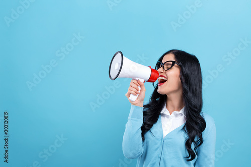 Young woman with a megaphone on a blue background Wallpaper Mural