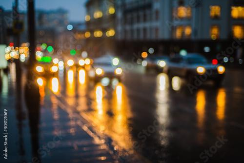 Obraz Wet night city street rain Bokeh reflection bright colorful lights puddles sidewalk Car - fototapety do salonu