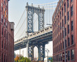 Iconic view of Manhattan Bridge from Washington Street. Red brick street buildings leading to the bridge at dusk. Brooklyn. NYC, USA
