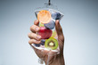 Human Hand Holding Saline Bag With Fruit Slices Over Grey Background