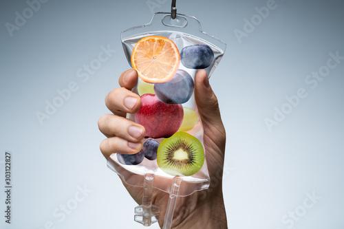Fototapeta Human Hand Holding Saline Bag With Fruit Slices Over Grey Background obraz