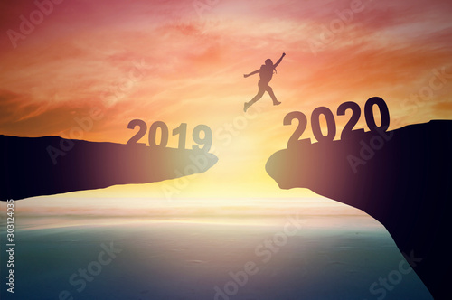 Obraz Jump to 2020 new year concept, silhouette of man jumping over  barrier cliff and success - fototapety do salonu