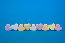 Sweet Candy Hearts (nine) On A Row Upon A Blue Surface