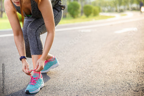 Pinturas sobre lienzo  Woman runner tying running shoes before run for exercise in the morning