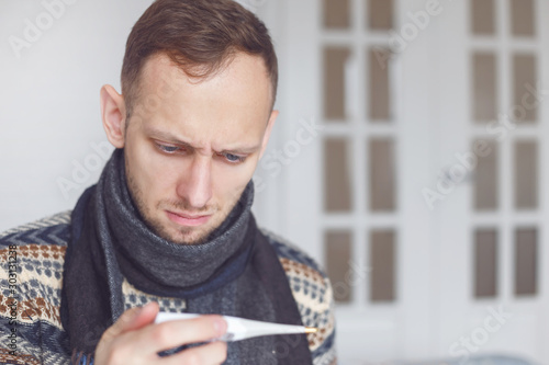 Sick man checking his temperature at home in the living room. Fototapet