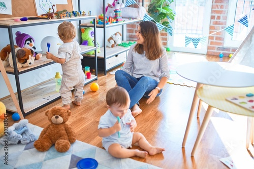 Obraz Beautiful teacher and toddlers playing around lots of toys at kindergarten - fototapety do salonu
