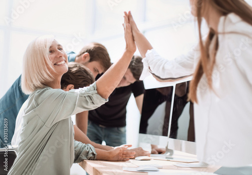 Obraz smiling employees giving each other a high five - fototapety do salonu