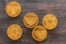 Chocolate Coins With Jewish Symbols On A Wooden Background.
