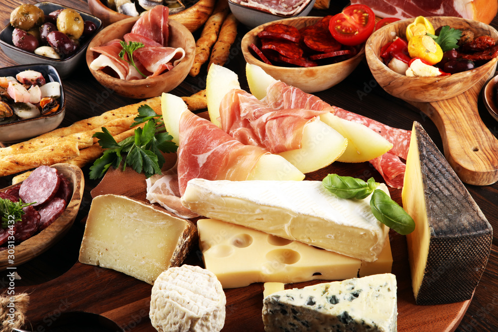Fototapeta Italian antipasti wine snacks set. Cheese variety, Mediterranean olives, seafood salad, Prosciutto di Parma, tomatoes, anchovy and wine in glasses