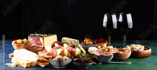 Obraz Italian antipasti wine snacks set. Cheese variety, Mediterranean olives, seafood salad, Prosciutto di Parma, tomatoes, anchovy and wine in glasses - fototapety do salonu