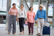 canvas print picture - group of four happy asian Senior  tourists walking on street in urban city outdoors.  old man Travellers lifestyle  . elderly women vacation . ageing society concept. pensioner traveling . mature